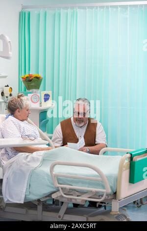 Senior man with greeting card visiting wife resting in hospital room - Stock Photo