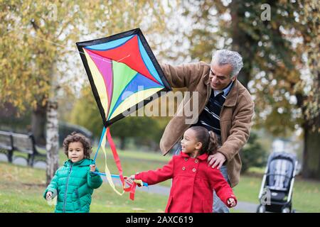 Grandfather and grandchildren flying a kite in autumn park - Stock Photo