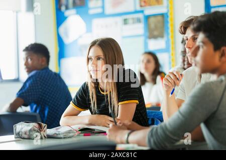 Close up focused, attentive high school girl student listening in classroom - Stock Photo