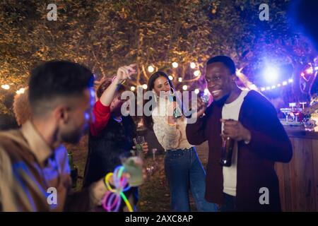 Friends dancing and singing karaoke at garden party - Stock Photo