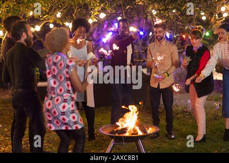 Friends with sparklers around fire pit at garden party - Stock Photo