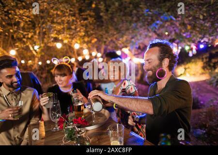 Man making cocktails for friends at garden party - Stock Photo