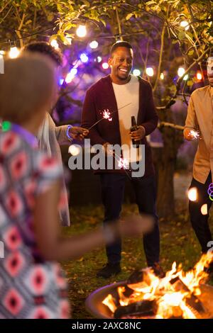 Friends with sparklers drinking beers around fire pit - Stock Photo