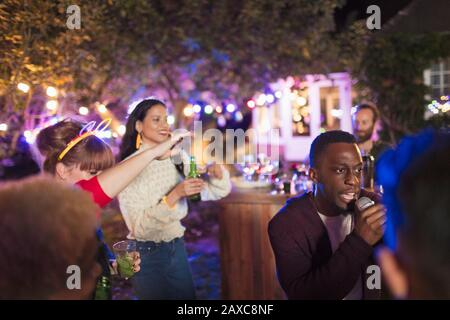 Friends drinking and singing karaoke at party - Stock Photo