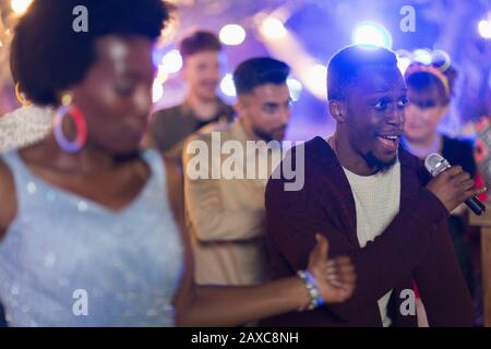 Friends signing karaoke and dancing at party - Stock Photo