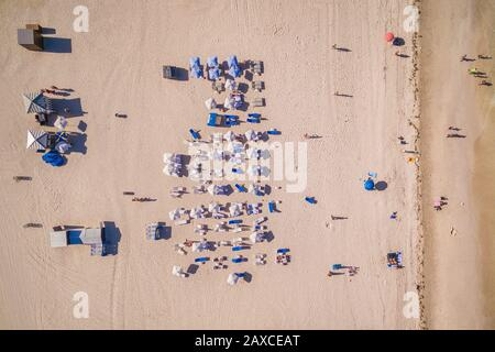 Top down aerial view of beach summer scene with white umbrellas and people sunbathing in Miami, Florida, USA.