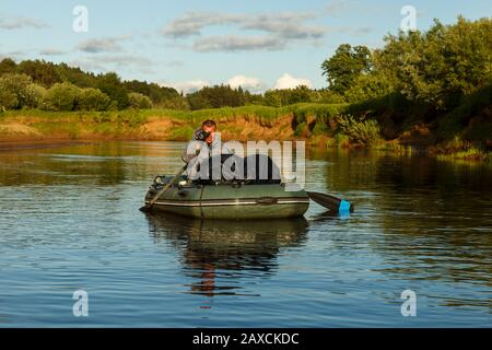 Tuzha, Russian - June 14, 2019: A man floats in a rubber boat on the Pizhma River. The fisherman is fishing. - Stock Photo