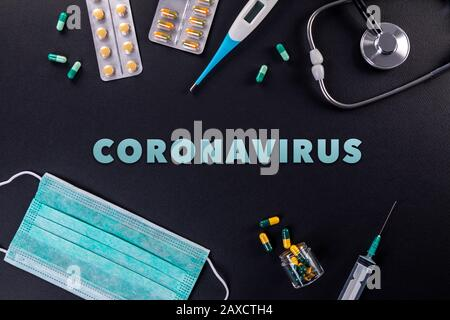 Protective masks, medicines, thermometer, stethoscope and syringe with coronavirus text on a black background. Novel coronavirus 2019-nCoV, MERS-Cov m - Stock Photo