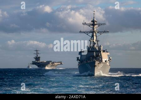 A U.S. Navy Nimitz-class nuclear powered aircraft carrier USS Theodore Roosevelt, Arleigh Burke-class guided-missile destroyers USS Russell and USS Pinckney transits the Pacific Ocean December 3, 2019 in the Pacific Ocean. - Stock Photo