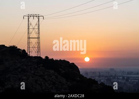 Electric power tower hilltop sunrise at Santa Susana Pass State Historic Park in Los Angeles California. Stock Photo