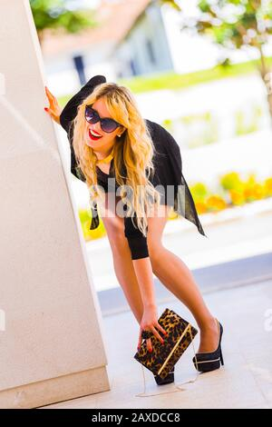 Young woman blonde blond fair-haired fairhair fairhaired legs in heels picking up raising fallen purse or handbag from ground floor laughing at camera - Stock Photo
