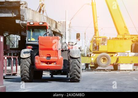Constuction site heavy machinery industrial background. Telescpic handler vehicle and big mobile crane working at city building development - Stock Photo