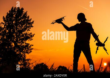 Small Drone Operator on the Fly Field During Scenic Sunset. Aerial Technologies. - Stock Photo