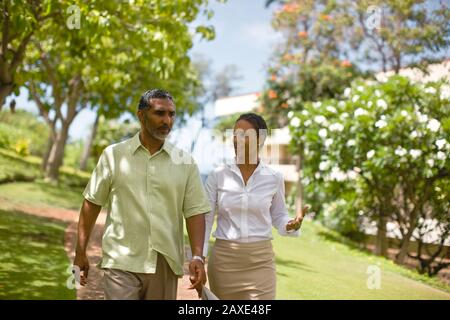 Couple in deep discussion while walking. - Stock Photo