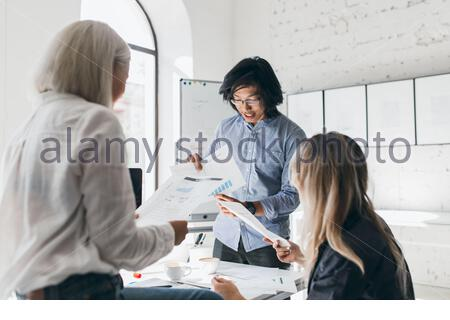 Young chinese man discussing new goals with cowokers and reading documents. Indoor portrait of busy students spending time in lecture hall while preparing for test. - Stock Photo