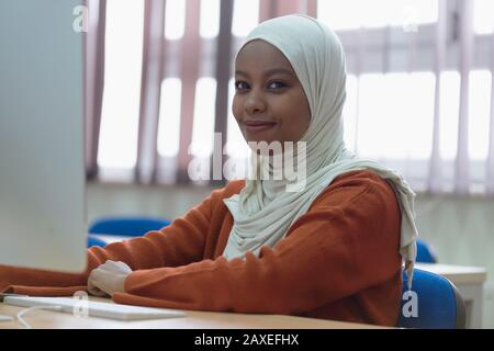 Beautiful female muslim african american IT student looking and smiling into camera. - Stock Photo