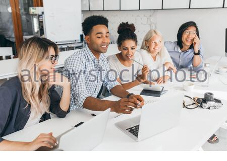 Interested african female student working on joint project with friends and using laptop. Indoor portrait of asian and european people spending time together after lecture. - Stock Photo