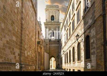 The narrow ancient alley leading to an arched doorway of the bell tower, outside the Duomo cathedral of Brindisi, Italy, in the Puglia region.