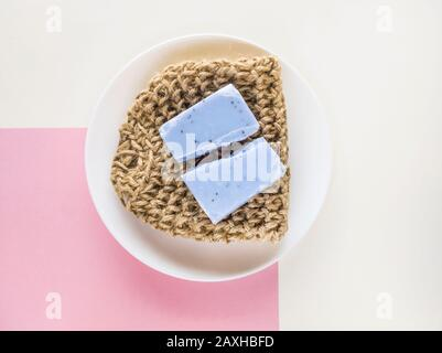 Homemade lavender soap bar and textile washcloth on minimalistic background. Set of plastic free and zero waste body care items. - Stock Photo