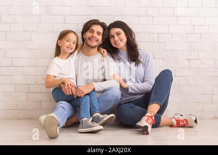 Happy Mom, Dad And Little Daughter Posing Together Sitting On Floor - Stock Photo
