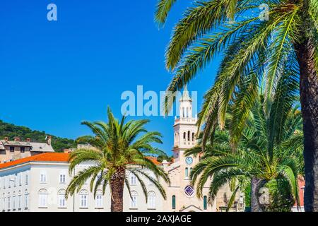 Croatia, beautiful city of Split, palms on Riva promenade and tower bell of st Francis church - Stock Photo