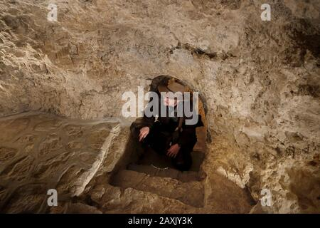 A tourist visiting a cave inside the Greek Orthodox Holy Monastery of Sarantarion Mountain or Temptation built on the slopes of the Mount of Temptation situated along a cliff overlooking the city of Jericho in the Palestinian Territories located near the Jordan River in the West Bank, Israel - Stock Photo