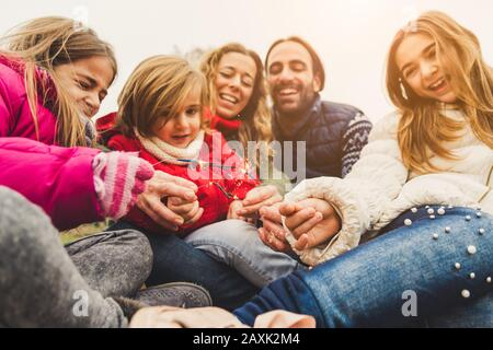 Happy family having a party outdoor celebrating with sparkler fireworks on new year's eve - Stock Photo