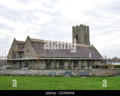 View of All Saints' and St Margaret's Church in Pakefield, Lowestoft with new thatch roof ridge and scaffolding. - Stock Photo