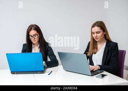 Two female co workers working on laptops in the office - Stock Photo