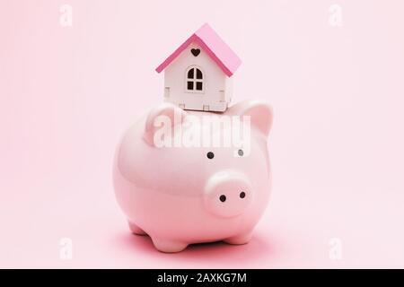 Toy house and piggy bank on a pink background. The concept of saving money to buy a house - Stock Photo