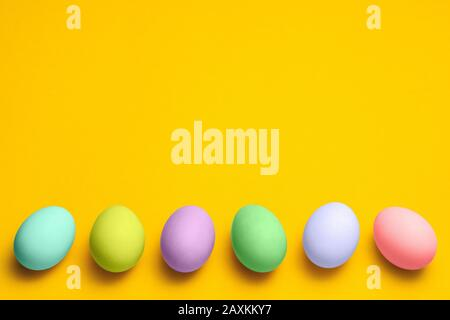 easter eggs painted in pastel colors on a yellow background with copyspace. easter advertise minimalist concept design - Stock Photo