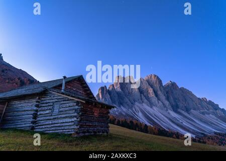 Autumn sunrise over the Odle Group seen from wood hut at Gampen Alm, Funes Valley, Dolomites, Bolzano, South Tyrol, Italy - Stock Photo