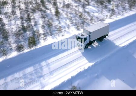 A lorry with a wagon rides along the road in winter. Winter road for a truck. - Stock Photo