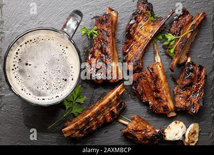Barbecue beef ribs with bbq sauce sliced on a stone board with beer mug. Top view flat lay - Stock Photo