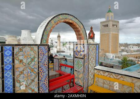 TUNIS, TUNISIA - DECEMBER 29 2019: Colorful tiled terrace overlooking the medina, with a view on the minaret of Ez Zitouna Mosque (Great Mosque) - Stock Photo