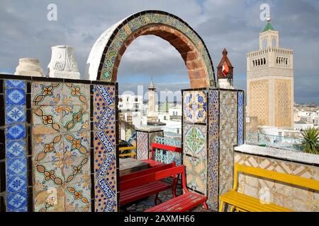 Colorful tiled terrace overlooking the medina in Tunis, Tunisia, with a view on the minaret of Ez Zitouna Mosque (Great Mosque) and the minaret of Ham - Stock Photo