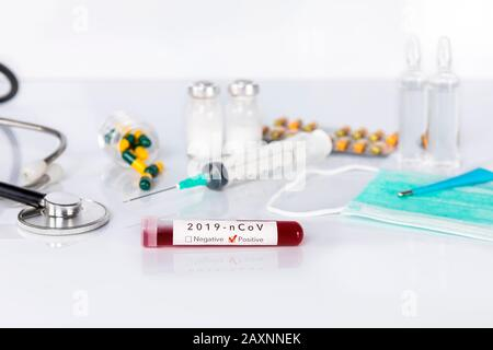 Blood test tube with the Coronavirus disease for virus test and research. Blood test tube with protective masks, medicines, thermometer, stethoscope a - Stock Photo