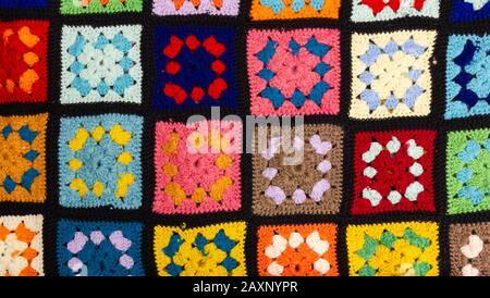 Detail of a crocheted patchwork multicolor wool blanket - Stock Photo