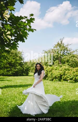 Young happy woman in white long dress has fun outdoors in a spring garden. Young bride with floral wreath in her wedding hairstyle spinning around and