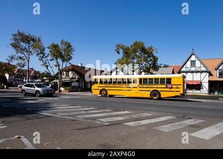 Santa Ynez Valley High School District yellow bus in the Danish town of Solvang in California, USA - Stock Photo