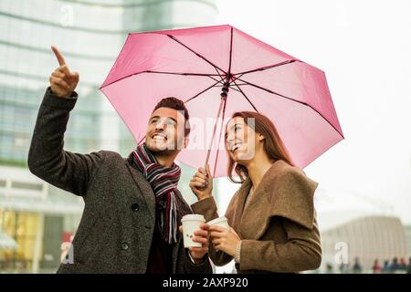Happy romantic couple with coffee take away paper cup under a umbrella in city center - Two lovers having fun outdoor drinking cappuccino - Winter con