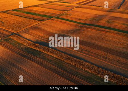 Colorful countryside patchwork background, cultivated agricultural field as abstract pattern in autumn sunset, aerial view from drone pov - Stock Photo