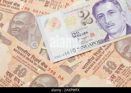 A close up image of a two dollar bill from Singapore close up in macro with Indian ten rupee bank notes - Stock Photo