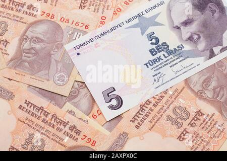 A close up image of a purple five Turkish lira bank note on a background of Indian ten rupee bank notes in macro - Stock Photo