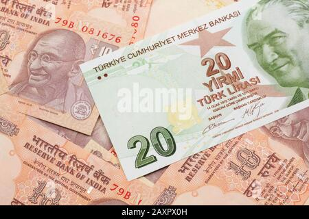 A close up image of a green twenty Turkish lira bank note on a background of Indian ten rupee bank notes in macro - Stock Photo