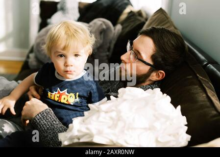 A young father cuddling with his son on the couch. - Stock Photo