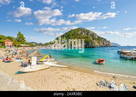 A sunny day at Palaiokastritsa beach as tourists sunbathe and swim in the sea on the island of Corfu, Greece. - Stock Photo