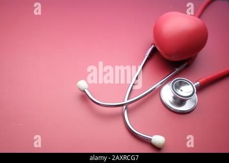 Closeup of heart shape and stethoscope on red background  - Stock Photo
