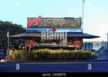 Harrys Cafe De Wheels famous pie cart caravan at Woolloomooloo, late afternoon, neon signs illuminated in rich colours - Stock Photo