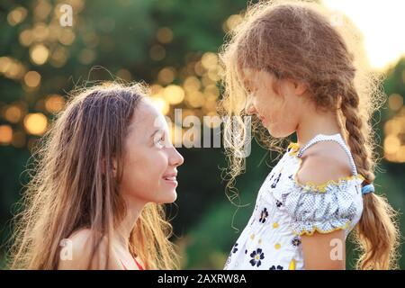 Two Cute little girls looking to each other and smiling at the  countryside. Happy kids spending time  outdoors
